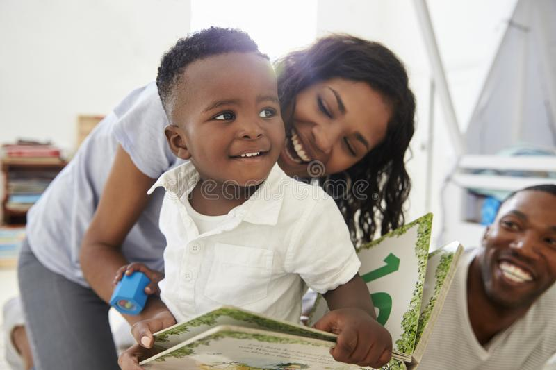 Family With Young Children Reading Book In Playroom Together stock photography