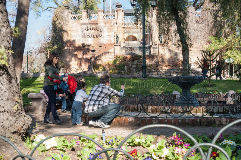 Family with young children stop to look at and photograph fountain in garden of Castle Hildago, Santiago. stock images