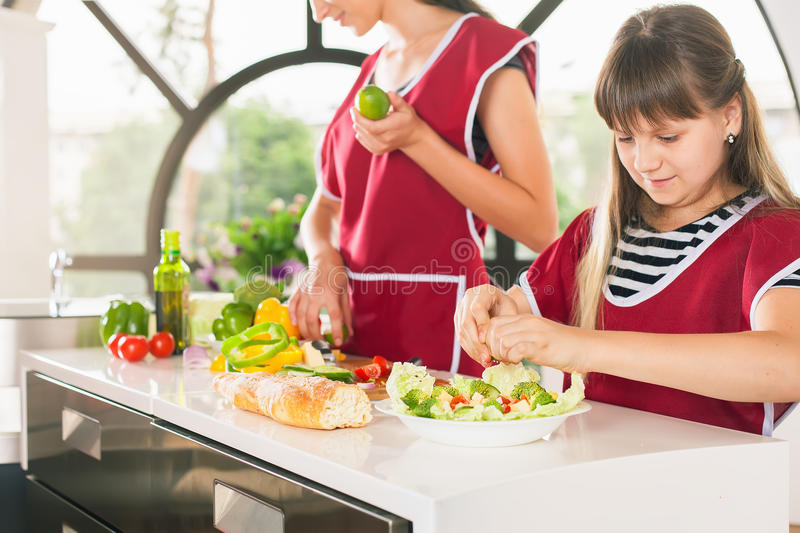 Family of young girls cooking. Recipe healthy food for kids. Closeup happy family of young girls cooking. Recipe healthy food for kids. Vegetarian meal at royalty free stock photography