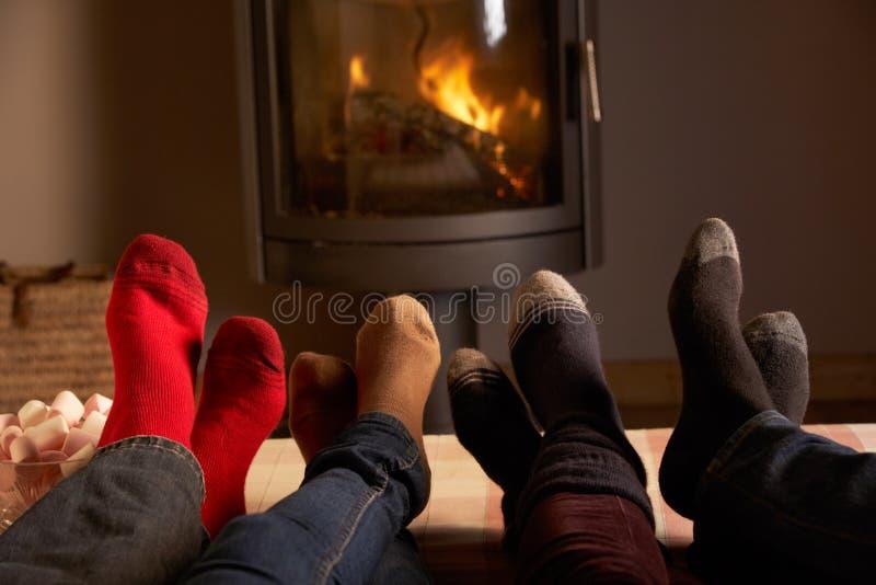 Familys Füße, die durch Cosy Protokoll-Feuer sich entspannen lizenzfreie stockfotos