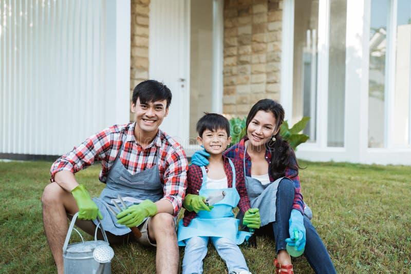 Famiy e bambino che si siedono su un'erba nel loro giardino della casa dopo il giardinaggio fotografia stock