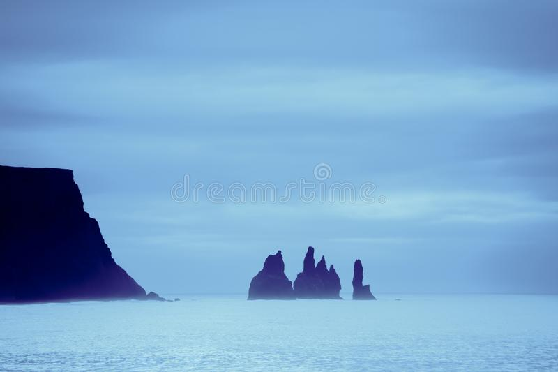 Famous basalt sea stacks of Reynisdrangar, rock formations on the black sand of Reynisfjar beach, view not far from Vik, a small v. Illage in southern Iceland royalty free stock images