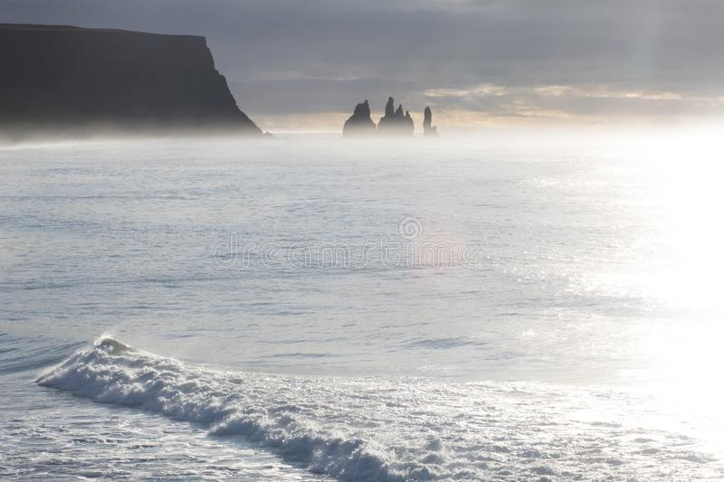 Famous basalt sea stacks of Reynisdrangar, rock formations on the black sand of Reynisfjar beach, view not far from Vik, a small v. Illage in southern Iceland stock photography