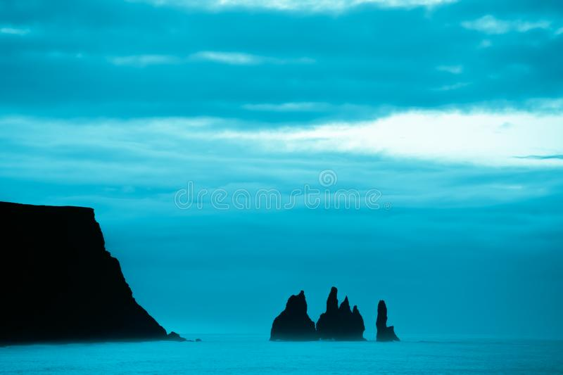 Famous basalt sea stacks of Reynisdrangar, rock formations on the black sand of Reynisfjar beach, view not far from Vik, a small v. Illage in southern Iceland stock photos