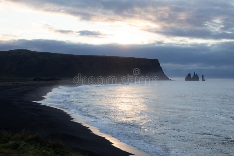 Famous basalt sea stacks of Reynisdrangar, rock formations on the black sand of Reynisfjar beach, view not far from Vik, a small v. Illage in southern Iceland stock photo