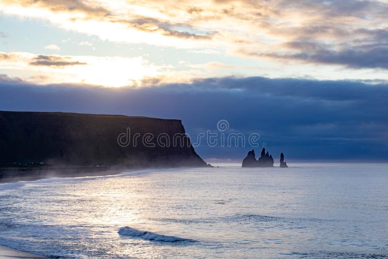 Famous basalt sea stacks of Reynisdrangar, rock formations on the black sand of Reynisfjar beach, view not far from Vik, a small v. Illage in southern Iceland stock image