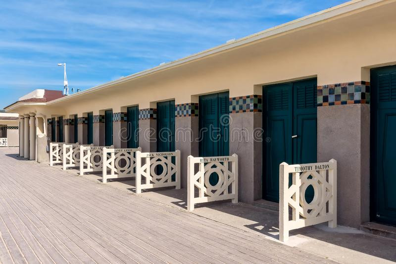 The famous beach cabins of the promenade des Planches in Deauville in France. Beach cabins marked with celebrity names of cinema in Deauville France stock images