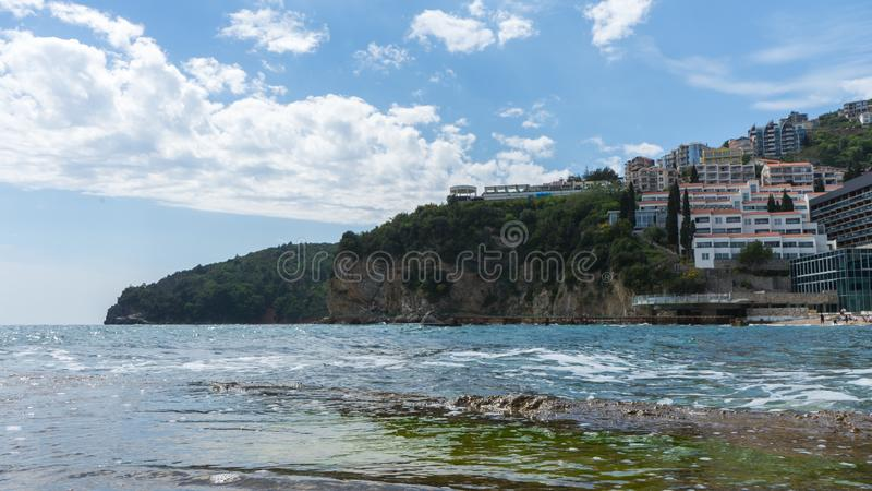 Famous beach resort. A view of the city of Budva and the Slovenska Plaza beach, Montenegro. Hotels in a cliff in the adriatic sea. Town, scenic, water, tourism royalty free stock photography