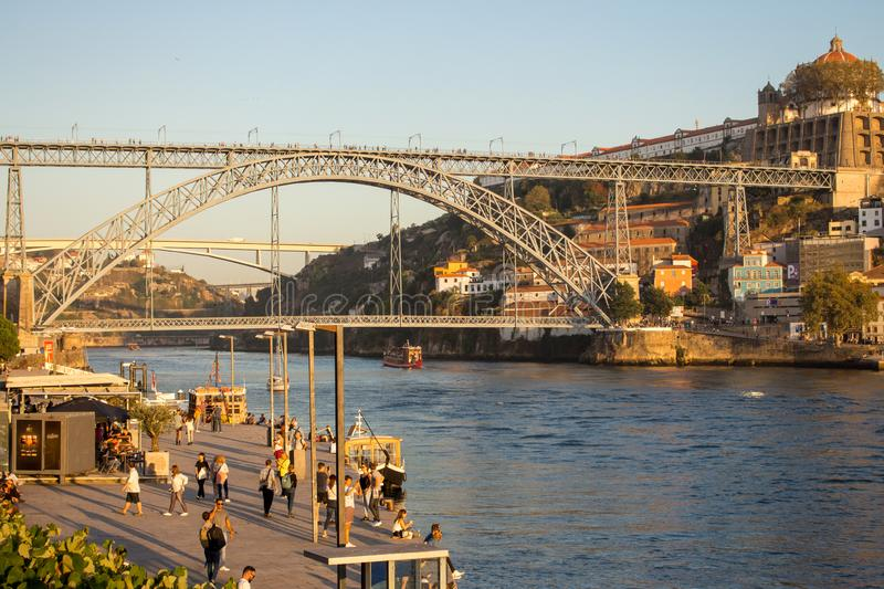 Famous bridge Ponte Luis in Porto bottom view. Riverside near giant steel bridge with people and boats. Porto, Portugal - 10/20/2019: Famous bridge Ponte Luis royalty free stock images