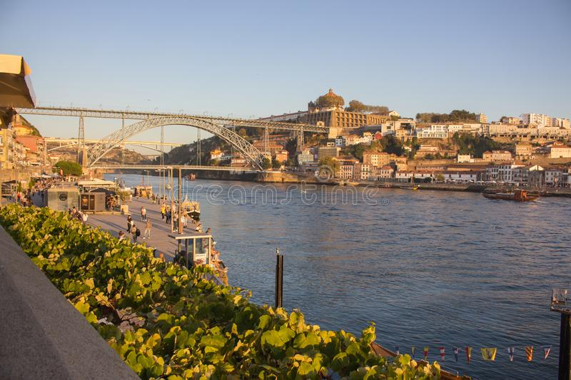 Famous bridge Ponte Luis in Porto bottom view. Riverside near giant steel bridge with people and boats. royalty free stock photo