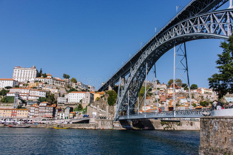 Famous bridge Ponte Luis in Porto bottom view. Riverside near giant steel bridge with people and boats. royalty free stock image