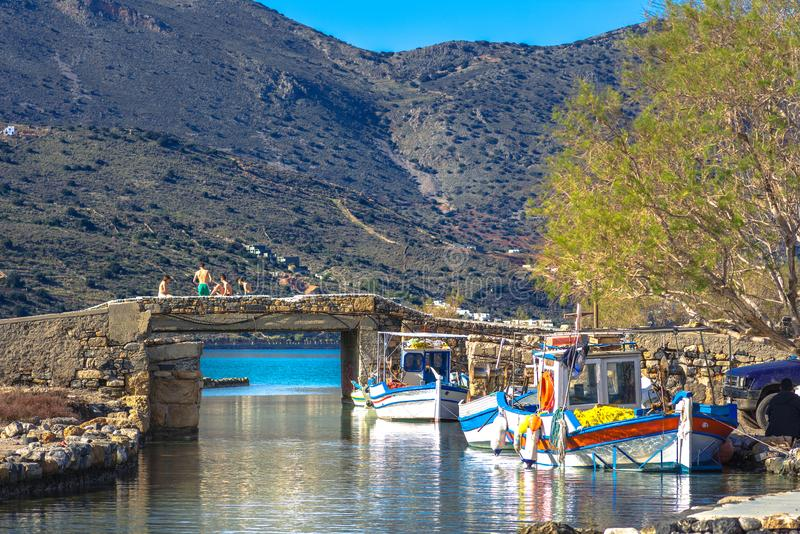 The famous canal of Elounda with the ruins of the old bridge, fishing boats and a group of young winter swimmers, Crete, Greece. royalty free stock image