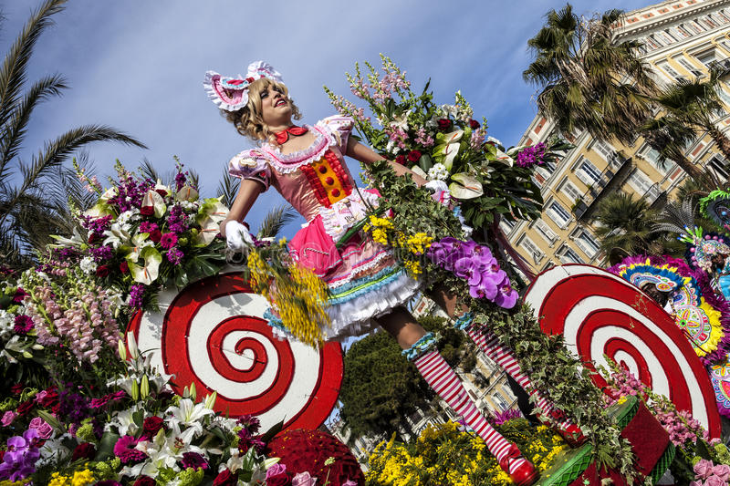Famous Carnival of Nice, Flowers` battle. Large float full of colored flowers and funny girls. NICE - FRANCE: Carnival of Nice, Flowers` battle. Large float full royalty free stock image