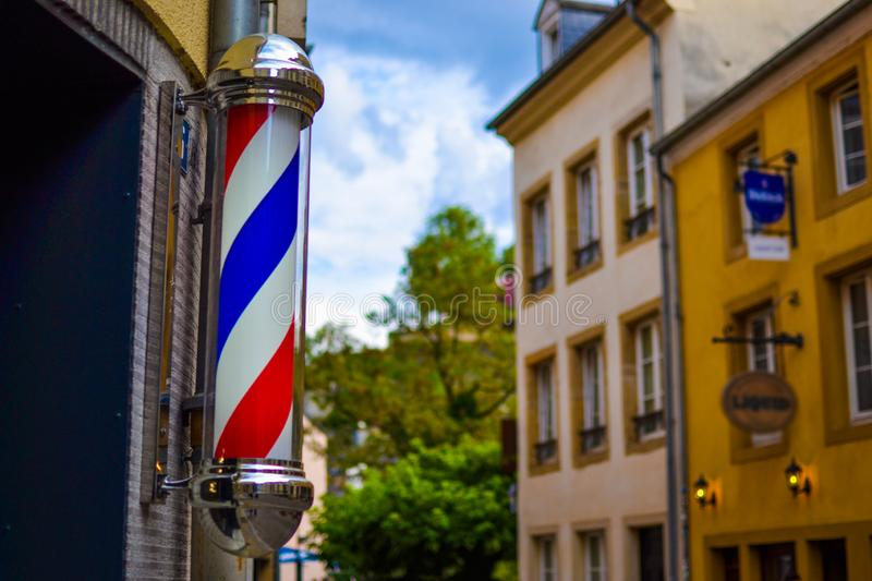 The famous and classic symbol of a barber shop. Close up of rotating red, white and blue barber shop light in Luxembourg, Europe royalty free stock images