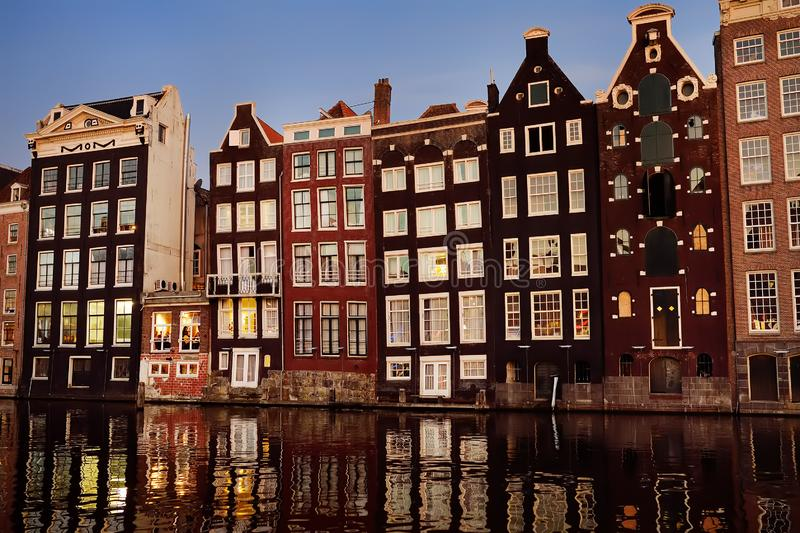 Famous dancing houses of the Damrak canal in Amsterdam on dusk royalty free stock photo