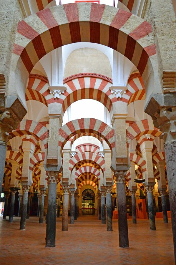 Interior - the famous double archwaysat the Mezquita Cordoba, Andalucia, Spain. The famous double archways and low lit vaulted ceiling at the Mezquita. The royalty free stock photo