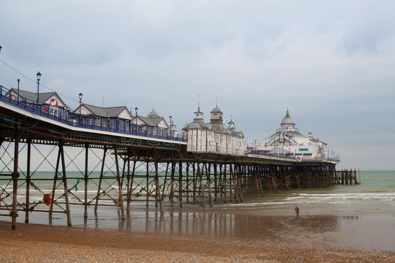 Famous Eastbourne Pier and beach in cloudy day. East Sussex, Eng. Eastbourne,England - May 20.,2012. Famous Eastbourne Pier and beach in cloudy day. East Sussex royalty free stock image