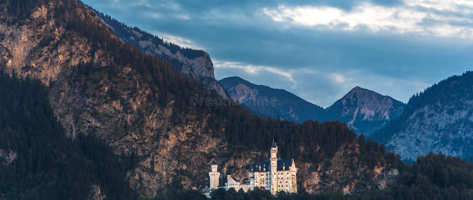 The famous fairytale Neuschwanstein castle in Bavaria and the Alps are painted with soft Golden sunlight at dawn royalty free stock photos