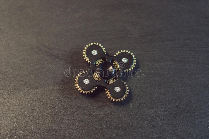 Famous fidget spinner stress relieving n a black wooden background royalty free stock images