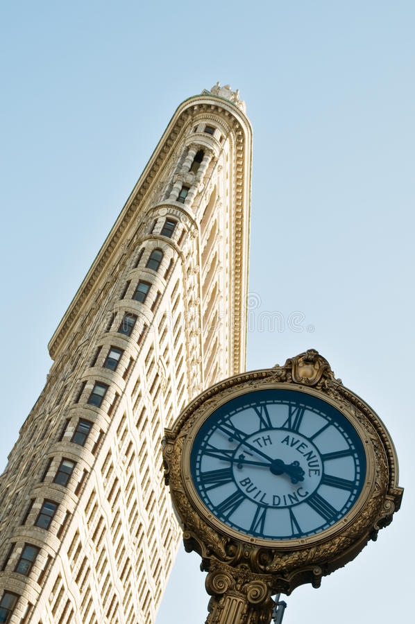 Famous flatiron building in New York City. Low angle view at the Flatiron building and street clock in New York City . The Flatiron Building, or Fuller Building royalty free stock photography