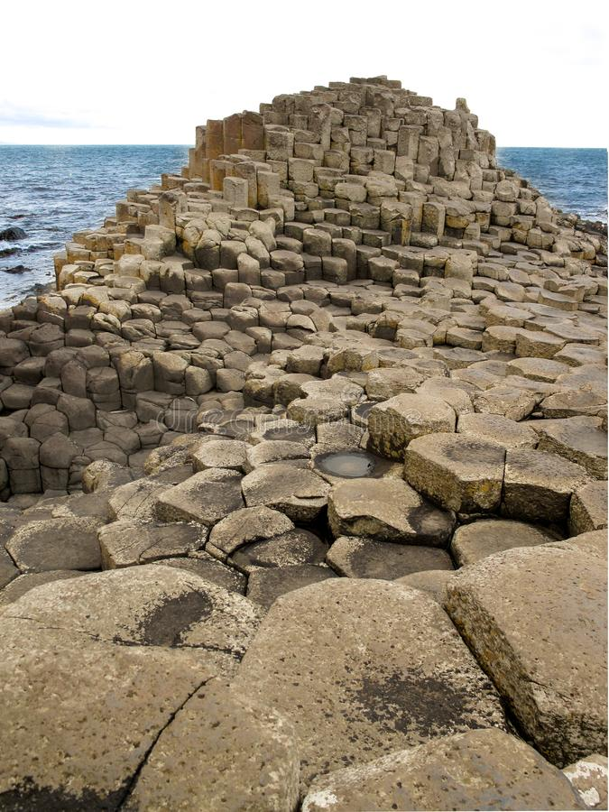 Famous Giant`s Causeway in Northern IreFamous Giant`s Causeway in Northern Ireland formed by hexagonal basalt columns that fell royalty free stock image