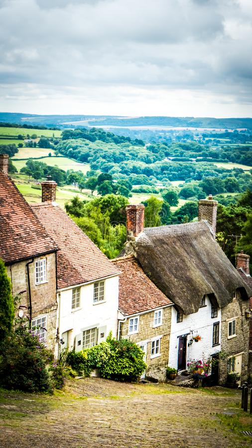 Famous Gold Hill cobbled street with old houses in Shaftesbury, UK. Gold Hill in Shaftesbury is an authentic place in the South of the UK. View of a stone old stock photography