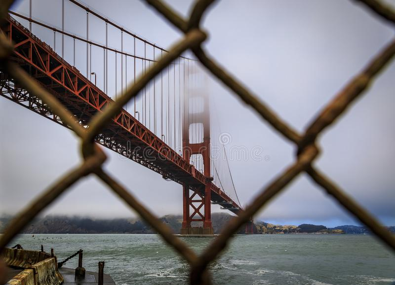 The famous Golden Gate bridge viewed through a rusty chain link fence on a cloudy day in San Francisco, California. The famous Golden Gate bridge viewed through royalty free stock image
