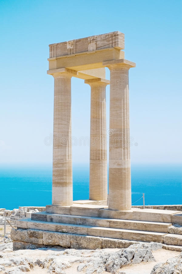 Famous Greek temple pillar against clear blue sky and sea in Greece stock image