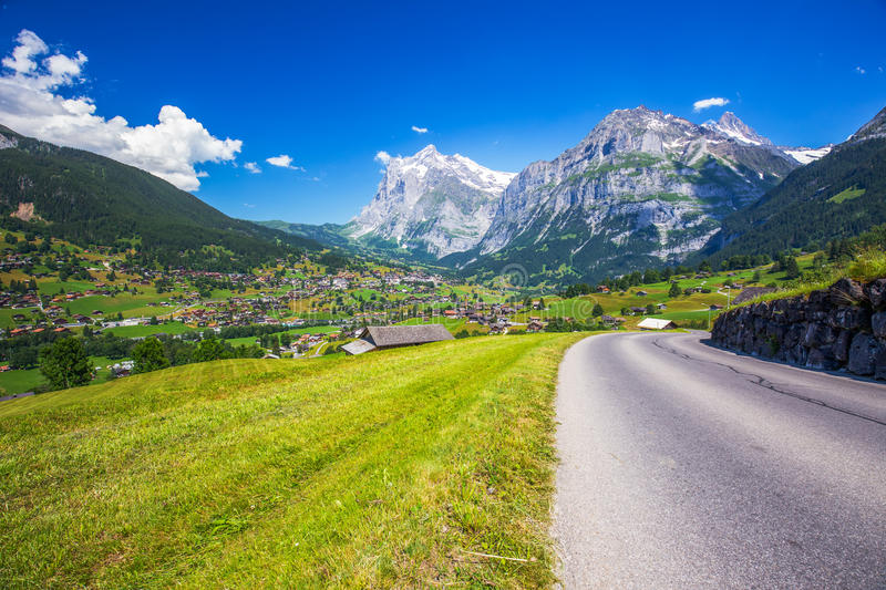Famous Grindelwald valley, green forest, Alps chalets and Swiss Alps, Switzerland stock photos