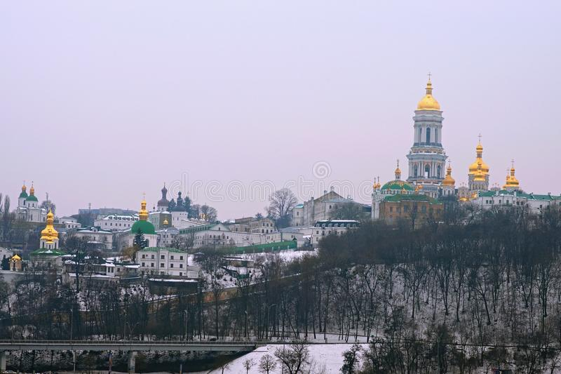 Famous Kyievo-Pechers`ka lavra and Belltower on blue sky background. It is a historic Orthodox Christian monastery. Morning landscape photo. Foggy winter stock images