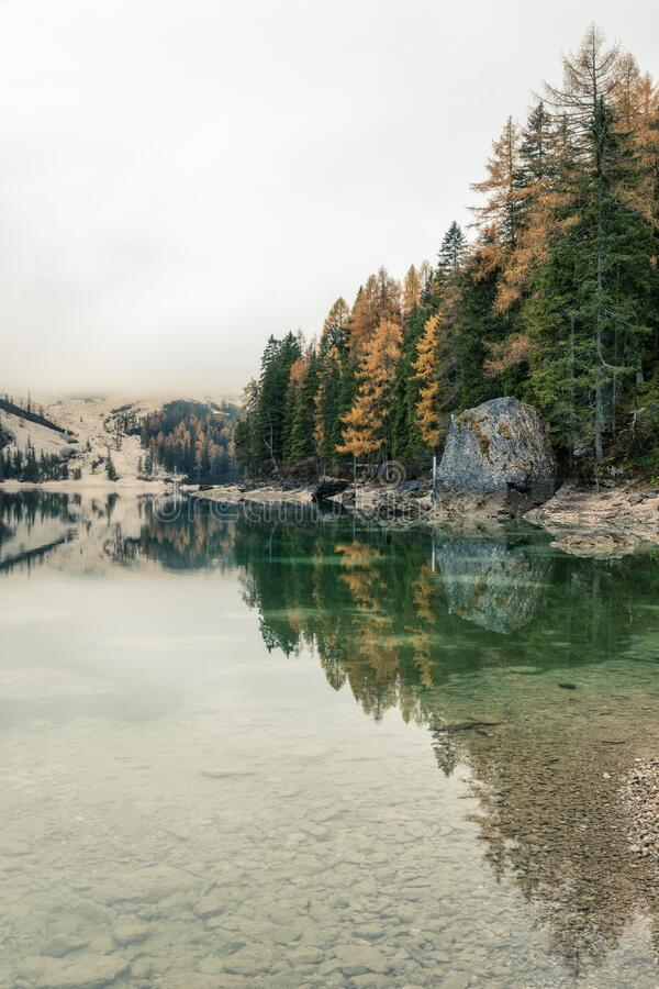 Famous Lago di Braies lake in Italy on a foggy weather with beautiful reflections. In autumn season stock photos