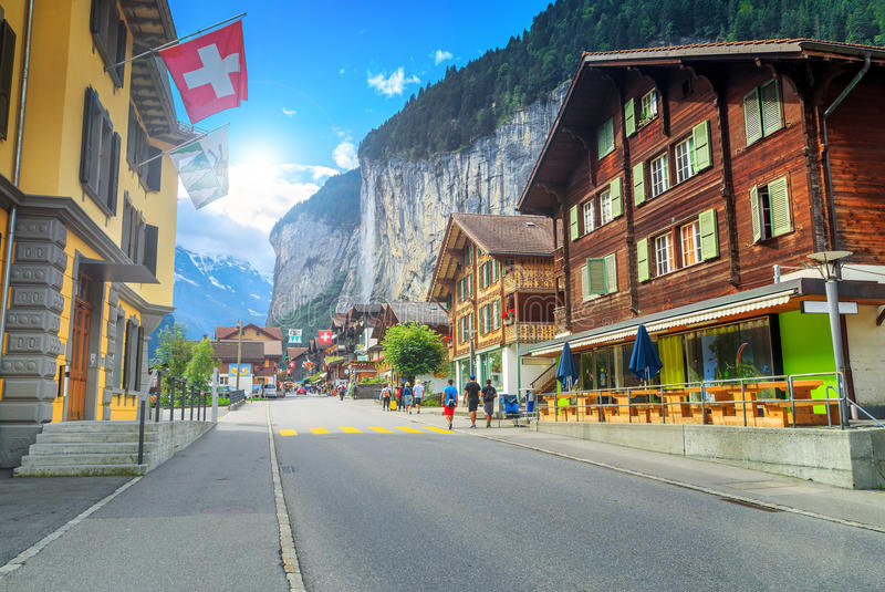 Famous Lauterbrunnen town and Staubbach waterfall,Bernese Oberland,Switzerland. Principal street of Lauterbrunnen with shops,hotels,terraces,swiss flags and royalty free stock image