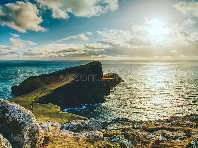 Famous look at Lighthouse on the cliff of Neist Point, rocky coast on the Isle of Skye royalty free stock images