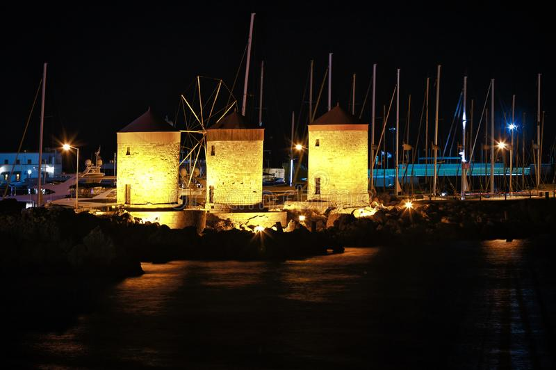 The famous mills of the island of Rhodes on pier among the stocks of yachts at night with beautiful lighting. stock photo