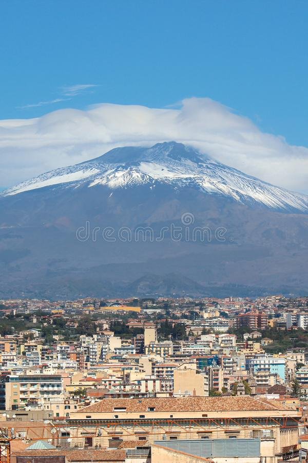 Famous Mount Etna volcano in Sicily, Italy captured on vertical picture with houses belonging to city Catania located at the foot. Of the mountain. Popular stock photography