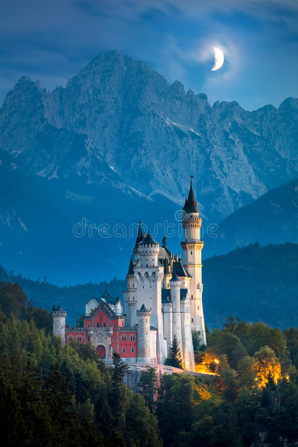 Famous Neuschwanstein Castle at night with moon and illumination. Beautiful view of world-famous Neuschwanstein Castle at night with moon and illumination royalty free stock photography