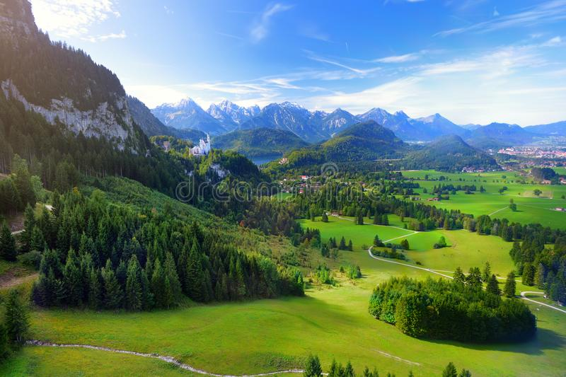 Famous Neuschwanstein Castle visible in the distance, located on a rugged hill above the village of Hohenschwangau in southwest Ba royalty free stock images