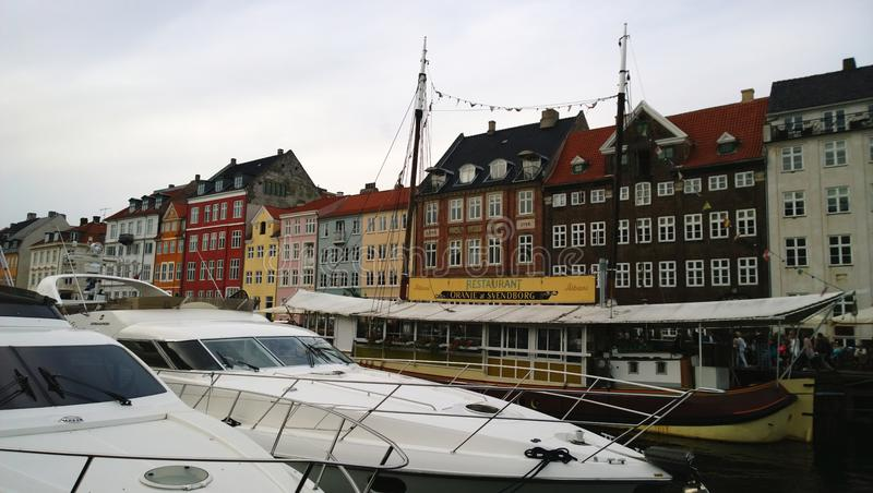 Famous Nyhavn in Copenhagen, with restaurants and expensive boats on the water stock photo