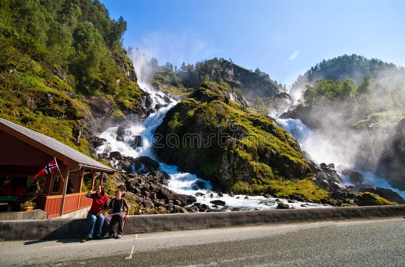 Famous Odda waterfalls, Norway. Two tourists sitting at the edge of the bridge at famous Odda waterfalls in Norway (Oddadalen royalty free stock photography