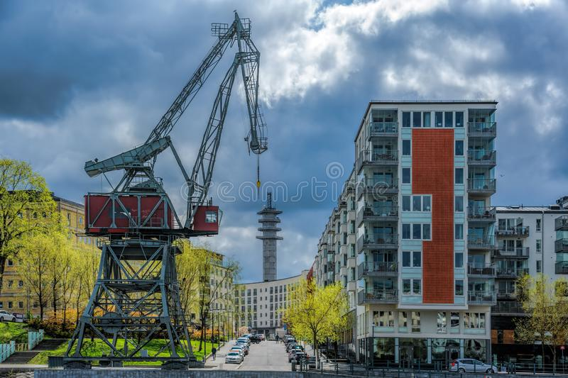 Famous old gantry port crane Lumakranen on the embankment of the canal Hammarby in front of modern houses. Stockholm, Sweden stock image