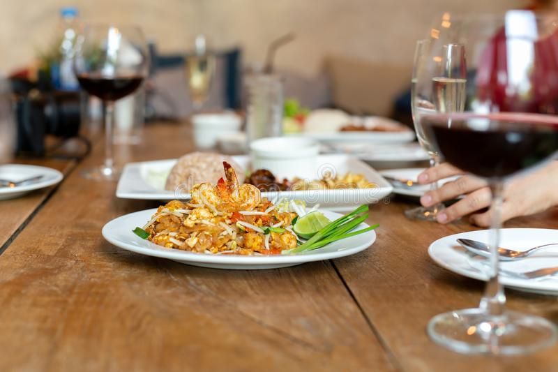 Famous Pad Thai noodles with shrimps and glass of red wine on wooden table. Famous Pad Thai noodles with shrimps and glass of red wine on wooden table stock photography