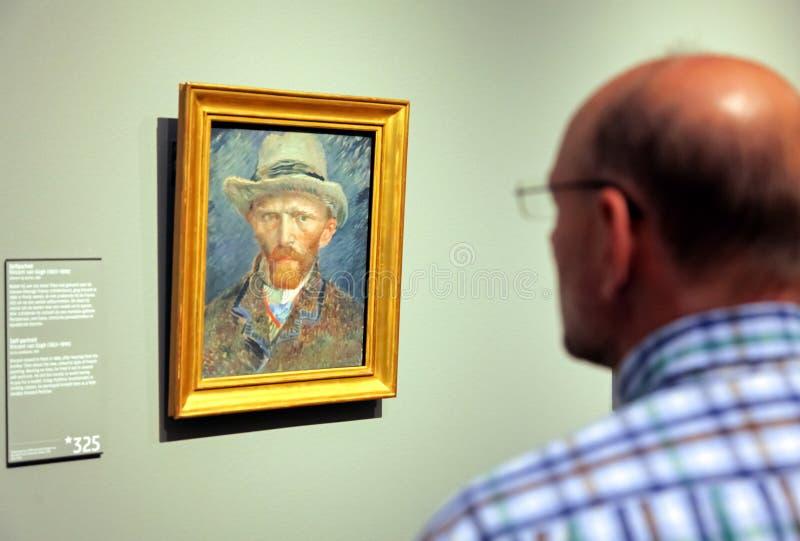 Famous painting Self-portrait by Vincent Van Gogh, Rijksmuseum -. AMSTERDAM, NETHERLANDS - APRIL 3: Visitor looking at self-portrait of Vincent Van Gogh in stock photo