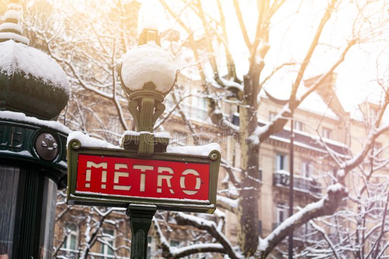 Famous Parisian metro sign covered with snow. Famous metro sign and trees covered with snow in winter, Paris, France stock photo