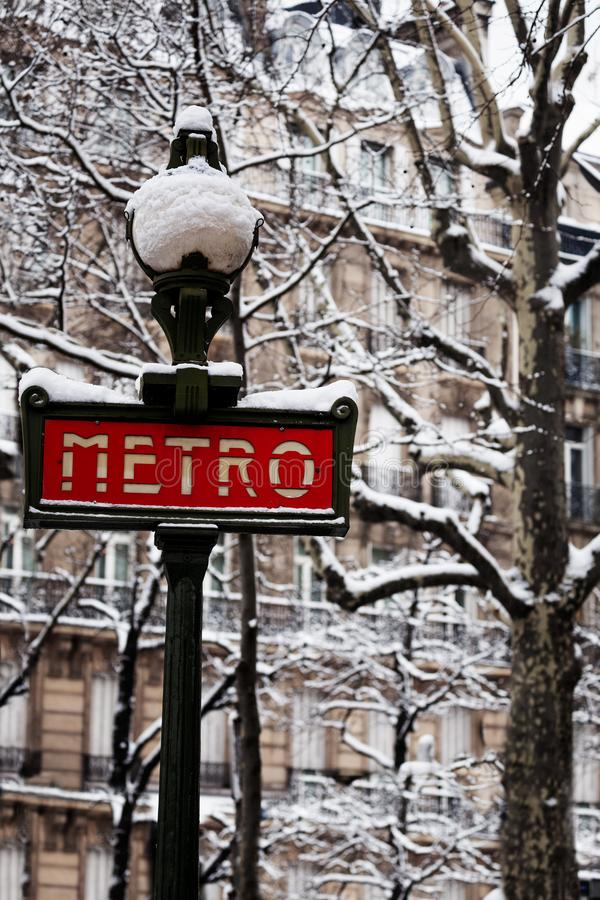 Famous Parisian metro sign after snowfall, France. Famous Parisian metro sign and trees after snowfall in winter, France, Europe royalty free stock photography