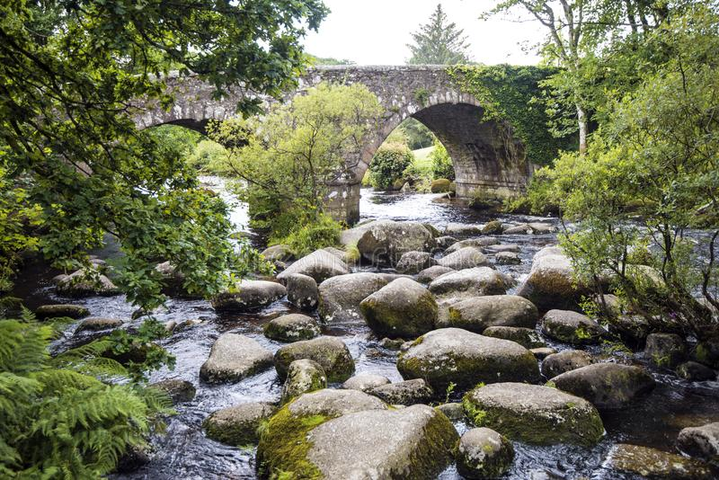 The famous picnic spot of Dartmeet, on Dartmoor, Devon, England. Children love to come here and paddle or clamber over the rocks of the Dart River which flows stock photography