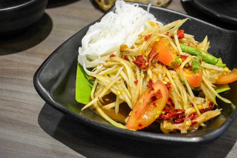 Famous and popular Thai street food, green papaya spicy salad with pickled fish or Som Tum served with Thai rice noodles stock photos
