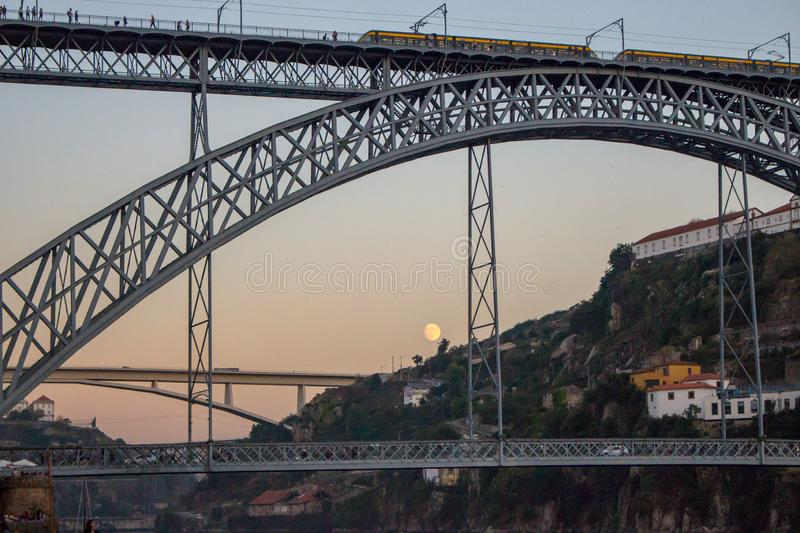 Famous Porto bridge Ponte Luis with train in the evening bottom view. Porto bridge in twilight with moon on background. Porto, Portugal - 10/20/2019: Famous stock images