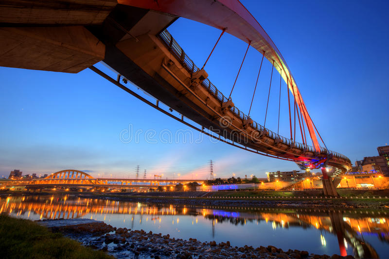 The famous Rainbow Bridge over Keelung River with reflections on smooth water at dusk in Taipei, Taiwan, Asia royalty free stock photo