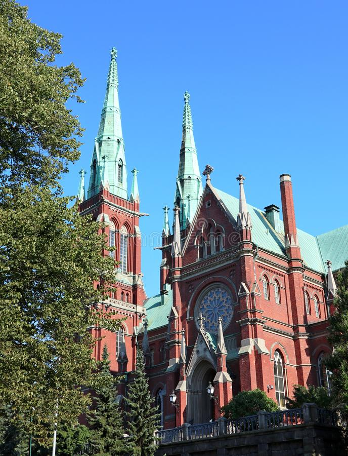 Famous red church historic architecture landmark in Helsinki, Finland with blue sky and vivid green grass royalty free stock photos
