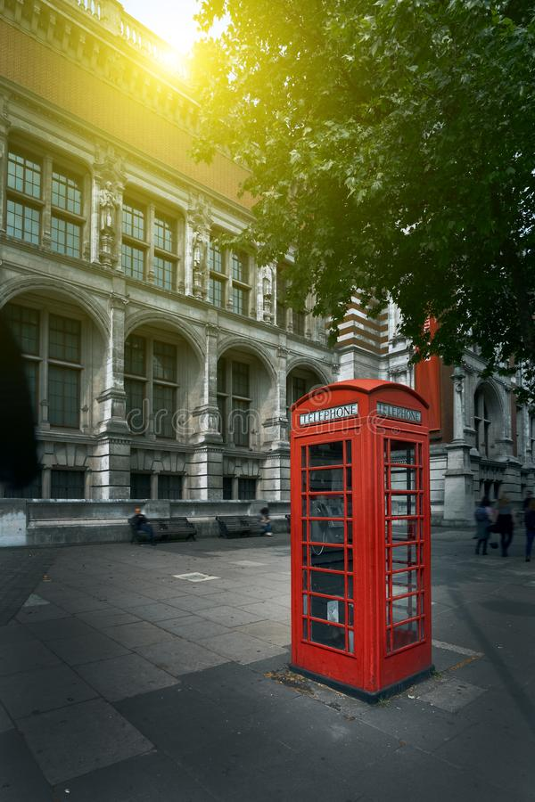 Famous red phone booth in London in the morning sun light. Movie poster concept. Toned.  stock photography